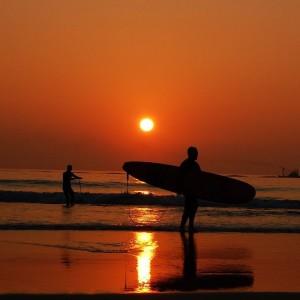 surfista com pescadores ao fundo